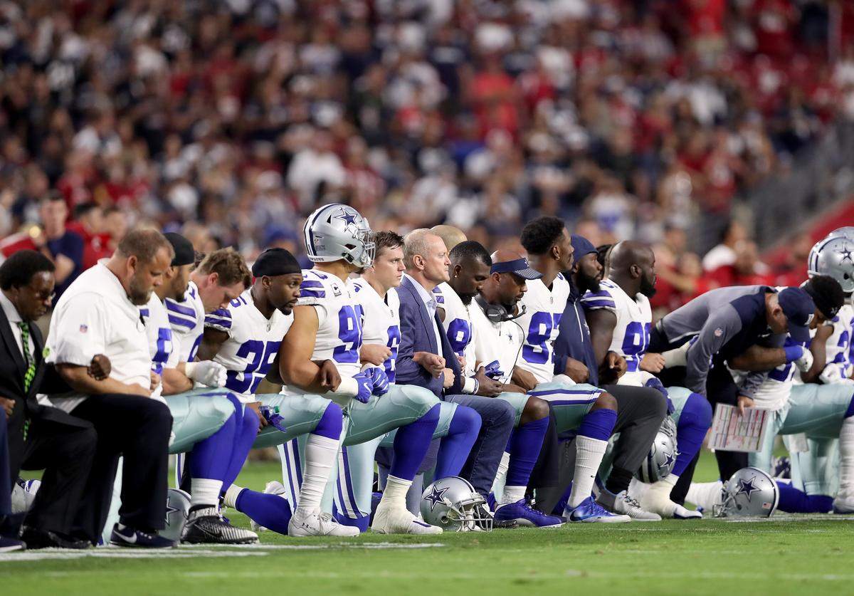 Dallas Cowboys link arms and kneel during the National Anthem before the start of the NFL game
