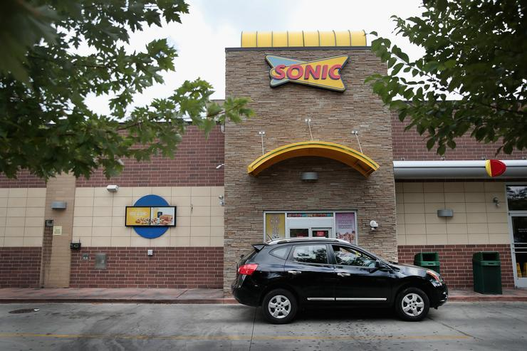 A customer picks up food at the drive-up window at a Sonic restaurant on September 25, 2018 in Chicago, Illinois. Inspire Brands Inc., the parent company of Arby's and Buffalo Wild Wings, announced today that it was buying Sonic for $2.3 billion.