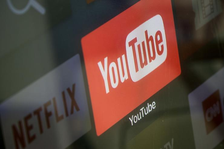 The YouTube and Netflix app logos are seen on a television screen on March 23, 2018 in Istanbul, Turkey