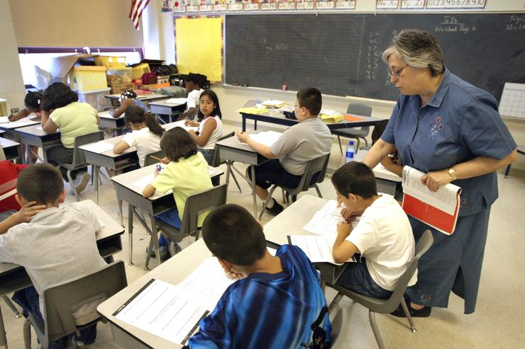 Arlene Lebowitz assists a student in her third-grade class during summer school July 2, 2003 in Chicago, Illinois
